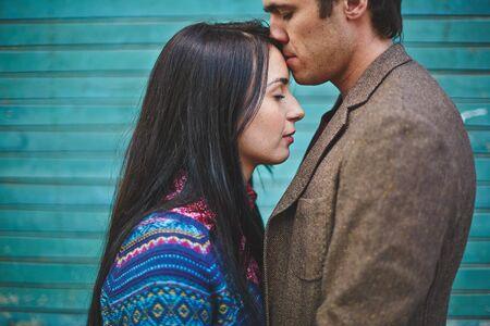 amorous woman: Amorous man kissing young woman on forehead