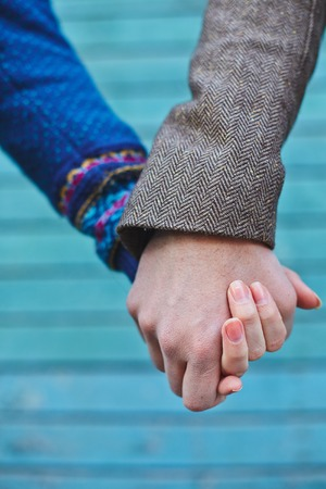 holding close: Hands of young couple over blue background