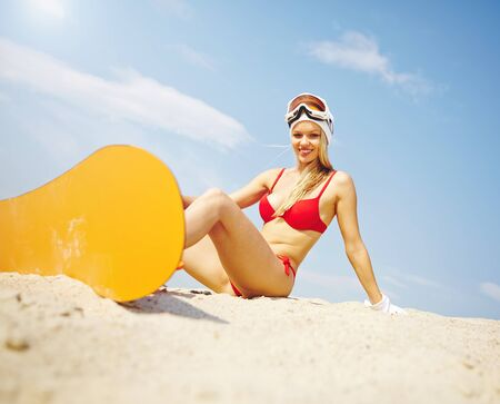 Active young woman with yellow sandboard sitting on sand photo