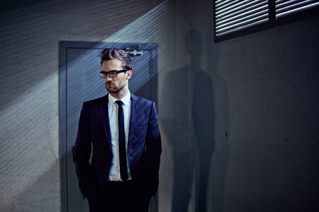young executive: Elegant young businessman standing by the door inside office building