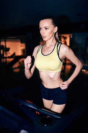 activewear: Fit girl in activewear running on treadmill in sports club