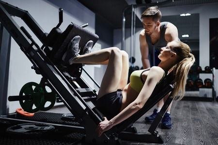 activewear: Fit woman exercising on facilities with her trainer near by Stock Photo