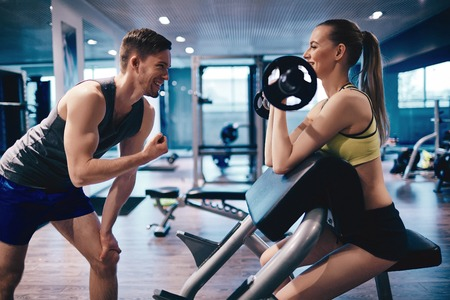 Young woman strengthening arm muscles in gym, her trainer encouraging her Archivio Fotografico