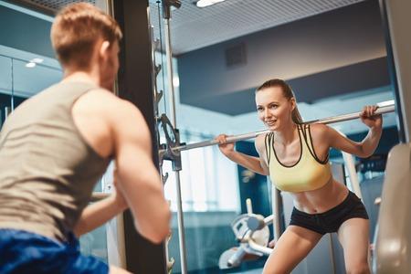fitness hombres: Hembra deportiva mirando a su entrenador durante el entrenamiento de pesas
