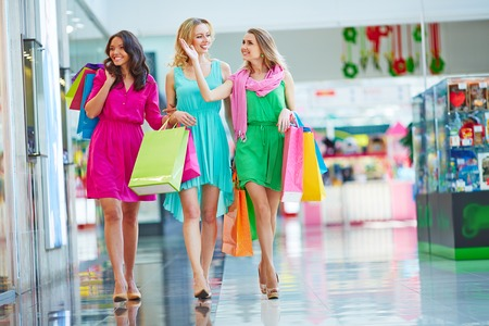 happy shopper: Beautiful girls with paperbags going down the mall Stock Photo