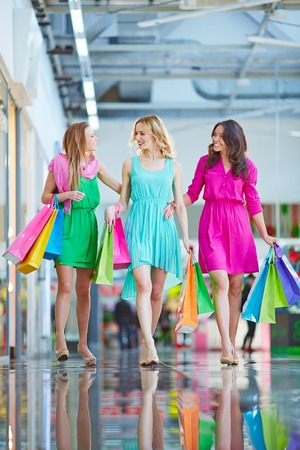 shopaholism: Modern girls with paperbags shopping in the mall