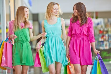 shopaholism: Modern girls with paperbags spending leisure in the mall