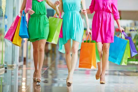 buyers: Group of shoppers in bright dresses walking in the mall Stock Photo