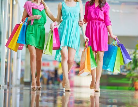 paperbags: Group of shoppers in bright dresses carrying paperbags