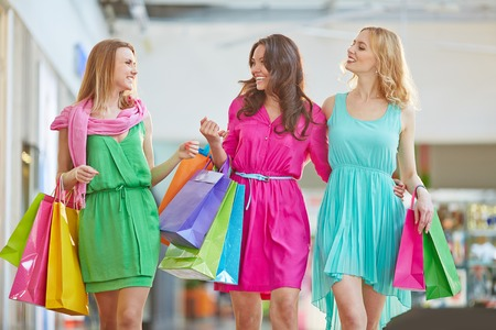 paperbags: Cute shopaholics with paperbags having talk in the mall