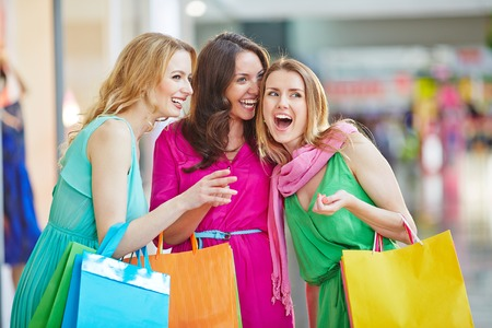 paperbags: Charming shopaholics with paperbags discussing something the saw in the mall Stock Photo