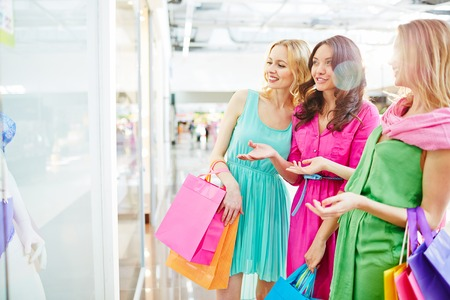 shopaholism: Charming girls with paperbags discussing lingerie in the shop window Stock Photo