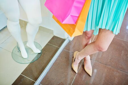 shopaholism: Legs of a shopper and those of mannequin in the mall Stock Photo