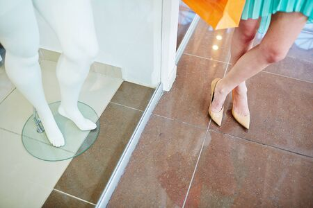 those: Legs of a shopper standing on the floor and those of mannequin in the shop window Stock Photo