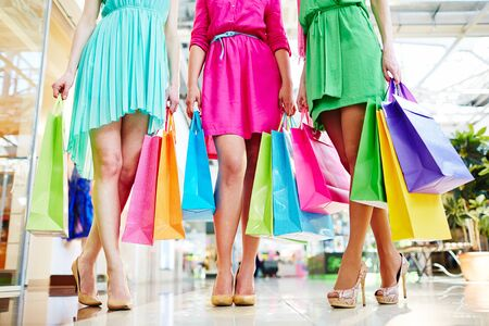 paperbags: Group of shoppers in bright dresses holding paperbags Stock Photo