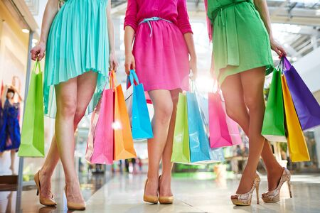 shopaholism: Three girls in bright dresses standing in the mall