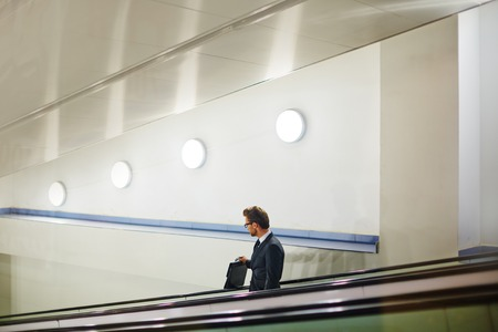 descending: Handsome businessman with briefcase descending on escalator Stock Photo
