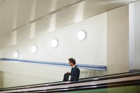 descending: Handsome businessman with briefcase descending on escalator Stock Photo