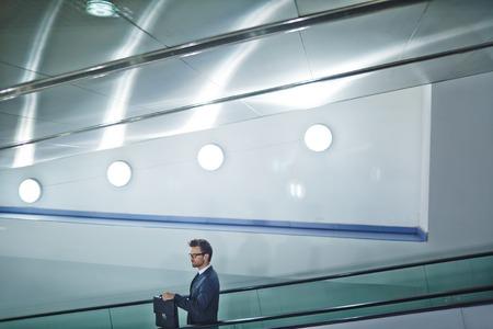 descending: Business agent with briefcase descending on escalator