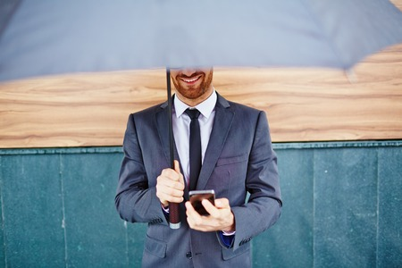 weather protection: Smiling employee with smartphone standing under umbrella