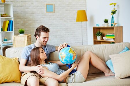 couple on couch: Happy young man and woman with globe choosing place for summer rest at leisure