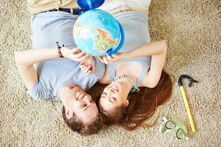 restful: Restful couple with globe lying on the floor and dreaming of summer vacations Stock Photo