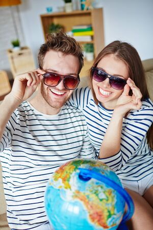 euphoric: Amorous couple in sunglasses looking at camera with toothy smiles