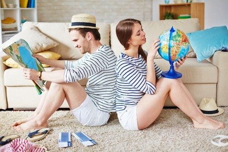 Young couple choosing place for travel while sitting at home