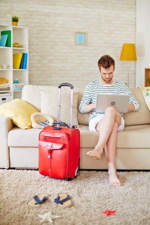 vacation home: Young man choosing tour in the net