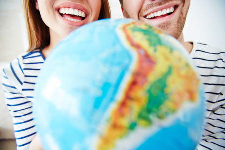 toothy smiles: Close-up of toothy smiles of couple and globe