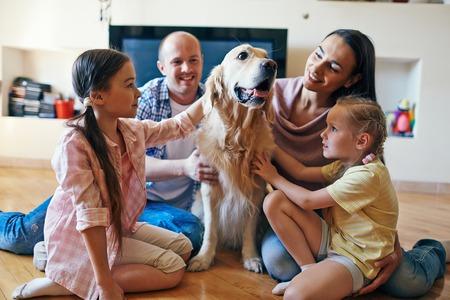 familias felices: PET rodeado de su familia de cuatro sentado en el sofá