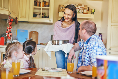 gathered: Family of four gathered in the kitchen for dinner Stock Photo