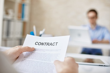 Working Environment: Contract in businessman hands in working environment Stock Photo