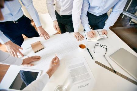 reunion de trabajo: Grupo de arquitectos con lápices en discusiones boceto en el lugar de trabajo Foto de archivo