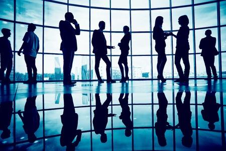 personas comunicandose: Contornos de la gente de negocios la comunicación contra la ventana en el interior del edificio de oficinas