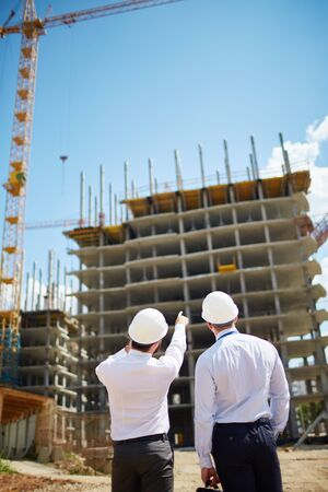 Male architects in helmets discussing new construction