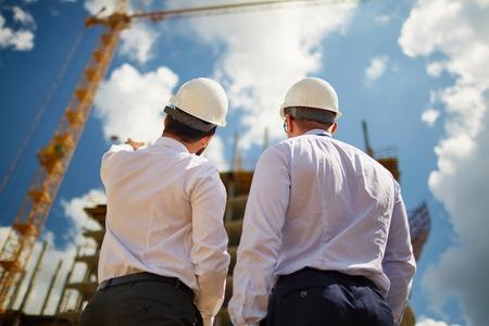 arquitecto: Arquitectos masculinos en cascos discusiones sobre la nueva construcci�n mientras est� de pie delante de �l Foto de archivo
