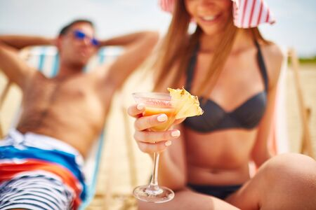 pineapple  glass: Glass of refreshing tropical cocktail held by young girl in bikini