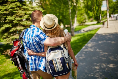 couples hug: Amorous couple with backpacks walking in urban environment