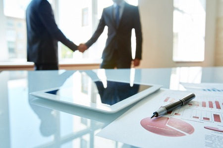 handshaking: Business objects at workplace with handshaking partners on background Stock Photo