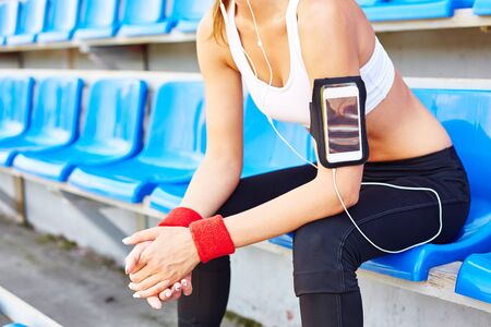 activewear: Modern girl in activewear sitting at stadium Stock Photo