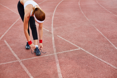 activewear: Fit girl in activewear tying her shoelace at stadium Stock Photo