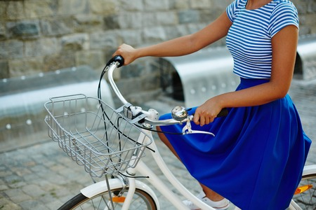 urban environment: Young female in retro clothes riding bicycle in urban environment Stock Photo