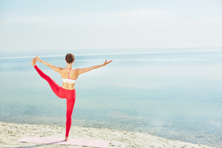 activewear: Sporty female in activewear stretching her leg while standing on the beach