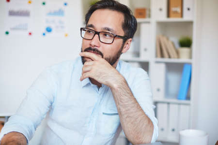 serious businessman: Pensive businessman in eyeglasses sitting in office Stock Photo