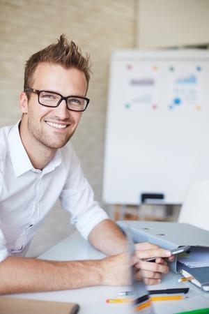 smiling businessman: Smiling businessman in eyeglasses looking at camera in office