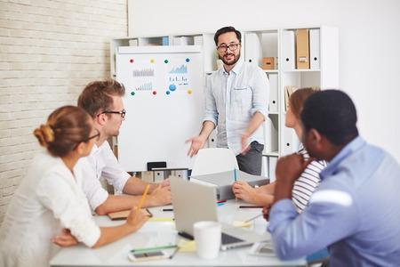 Modern medewerkers luisteren naar knappe leraar uit te leggen onderwerp op seminar