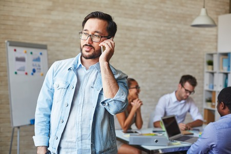 casual office: Asian businessman in eyeglasses speaking on cellphone in working environment Stock Photo
