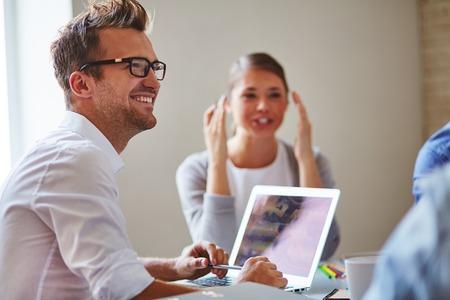 Vrolijke zakenman in brillen op zoek naar collega's met een glimlach