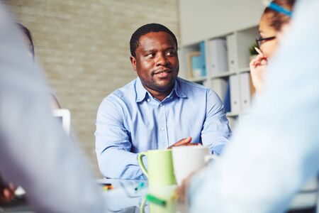 corporate meeting: African-american businessman looking at colleague at meeting
